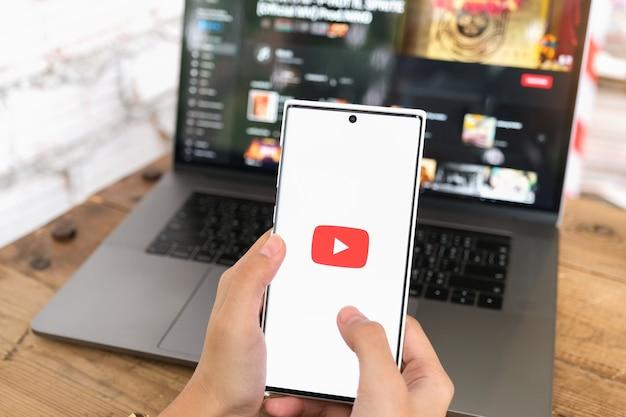 Chiang mai, thailand - 06. juni 2021: frau, die smartphone-handy mit videodienst youtube auf dem bildschirm hält.