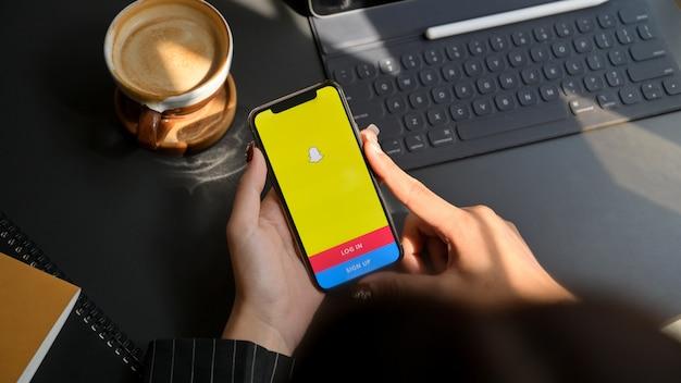 Chiang mai, thailand - 1. februar 2020: frau, die iphone mit snapchat-bildschirm hält. snapchat ist eine multimedia-messaging-app