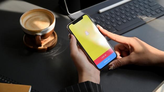 Chiang mai, thailand - 1. februar 2020: frau, die iphone mit snapchat-bildschirm verwendet. snapchat ist eine multimedia-messaging-app