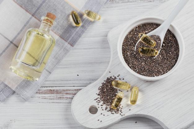 Chiasamen in der kleinen schüssel und in den gelatinekapseln mit omega-öl auf weißem hölzernem hintergrund. draufsicht