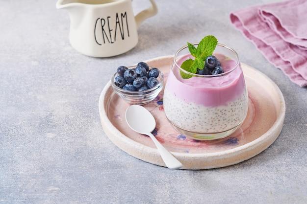 Chiasamenpudding mit blaubeerjoghurt und frischen beeren in glas für gesundes frühstück zubereitet. selektiver fokus.