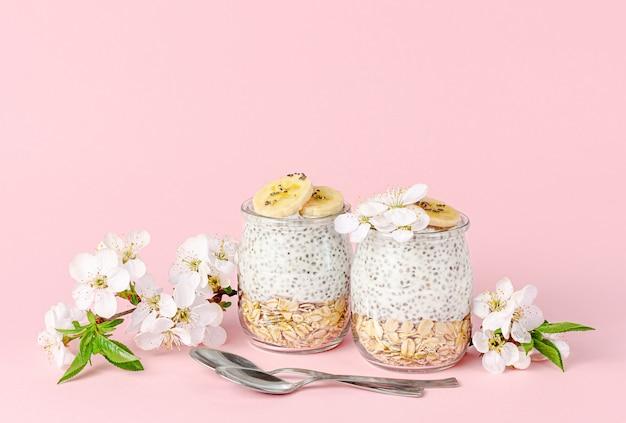 Chiasamenpudding mit joghurt, banane und hafer auf pastellrosa tisch. superfood-konzept. speicherplatz kopieren