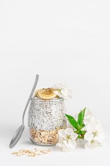 Chiasamenpudding mit joghurt und hafer auf weißem tisch mit blumen verziert. superfood-konzept. speicherplatz kopieren