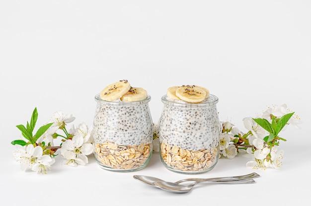 Chiasamenpudding mit joghurt und hafer auf weißer wand verziert mit blumen. superfood-konzept. speicherplatz kopieren