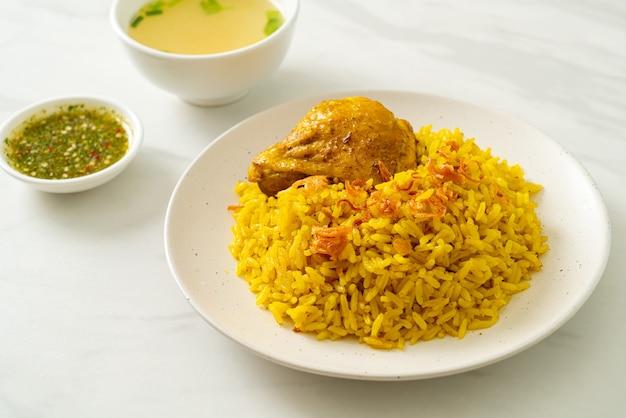 Chicken biryani oder curryreis und hühnchen. thai-muslimische version von indischem biryani, mit duftendem gelben reis und hühnchen.