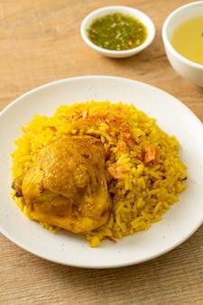 Chicken biryani oder curryreis und hühnchen - thailändisch-muslimische version des indischen biryani, mit duftendem gelbem reis und hühnchen - muslimische küche