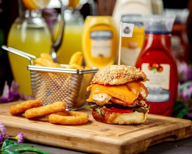 Chicken burger mit cheddar, serviert mit pommes frites und sauce