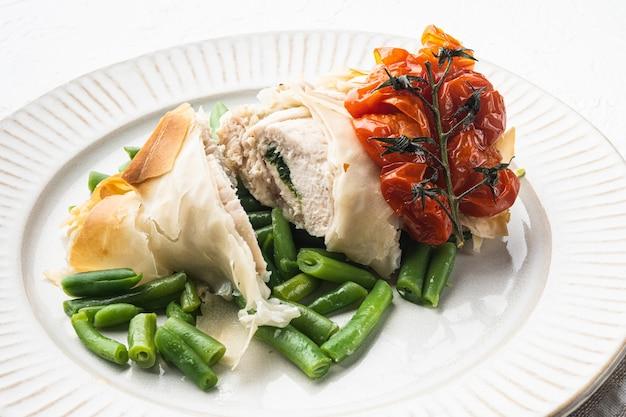 Chicken kiew filo-set, mit gebackenen kirschtomaten und grünen bohnen, auf weißem stein