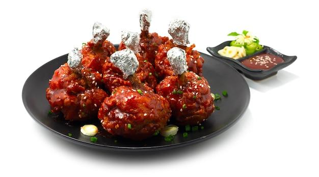 Chicken lollipops korean food style frittiert mit sauce vorspeisen gericht köstlich lecker serviert kochujang sauce dekoration mit knoblauch und chili seitenansicht