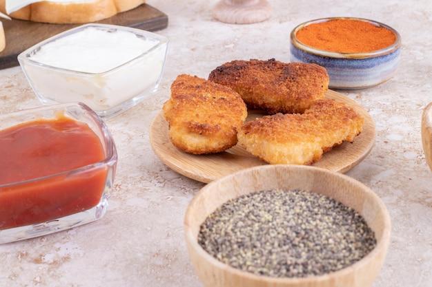 Chicken nuggets auf einem holzbrett mit saucen beiseite.