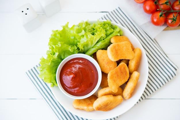 Chicken nuggets mit sauce und kräutern in einem teller, ansicht von oben