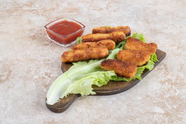 Chicken nuggets und bratwürste auf einem grünen salatblatt auf einem holzbrett.