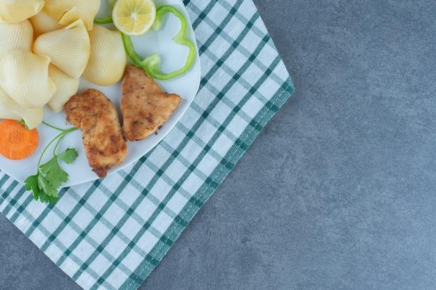 Chicken nuggets und gekochte nudeln auf weißem teller.