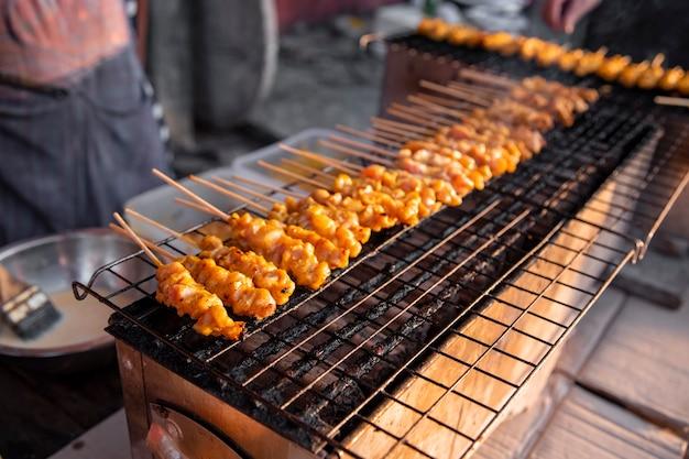 Chicken satay gegrillt auf grillplatte mit rauch. asiatisches streetfood