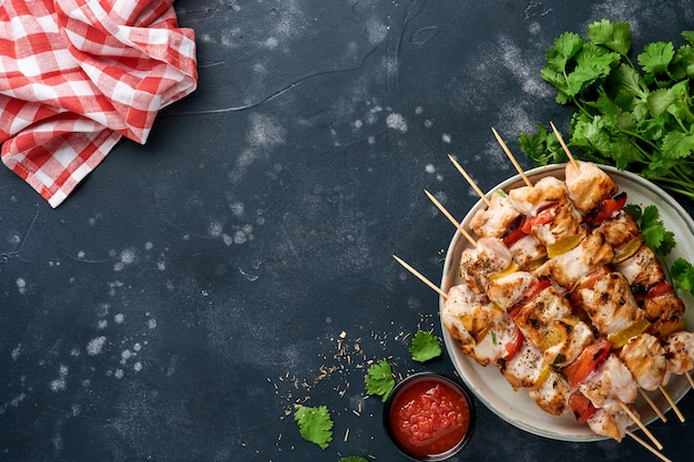 Chicken shish kebab oder spieße kebab auf holzbrett, gewürzen, kräutern und gemüse auf dunkelgrauem hintergrund. barbecue rohe zutaten für gulasch oder schaschlik. ansicht von oben. freier kopienraum