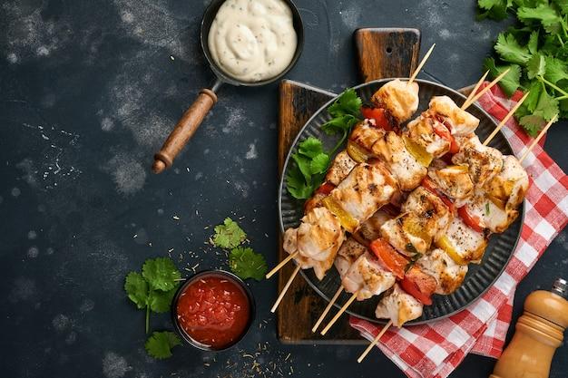 Chicken shish kebab oder spieße kebab auf holzbrett, gewürzen, kräutern und gemüse auf dunkelgrauem hintergrund. barbecue rohe zutaten für gulasch oder schaschlik. ansicht von oben. freier kopienraum.