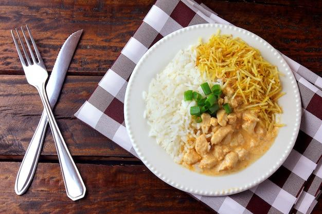 Chicken stroganoff ist ein gericht aus der russischen küche, das in brasilien aus saurer sahne mit tomatenextrakt, reis und kartoffelchips besteht.