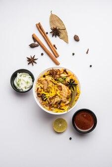 Chicken tikka biryani im restaurantstil verpackt für die lieferung nach hause in einer plastikbox oder einem behälter mit raita und salan