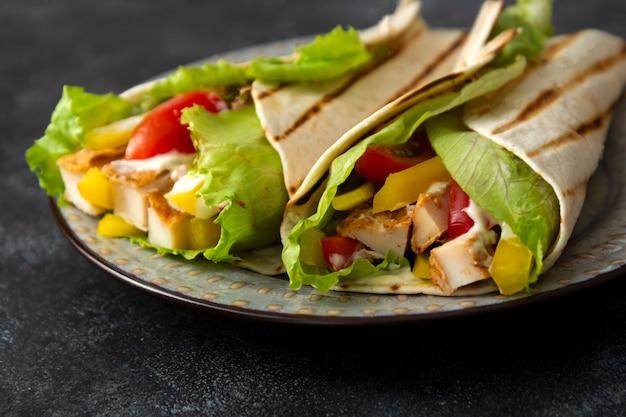 Chicken wrap sandwich mit frischem gemüse. leckeres gesundes essen auf dunklem hintergrund