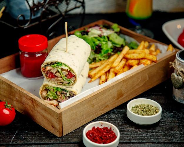 Chicken wrap serviert mit pommes frites salat salat und sauce