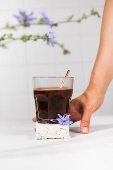Chicorée-getränk in einem transparenten becher mit chicorée-blüten im vordergrund