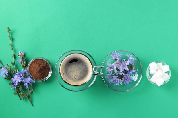 Chicorée-getränk in glasschale, mit konzentrat, zucker und blumen auf grünem hintergrund. gesundes kräutergetränk, kaffeeersatz, draufsicht, platz für text