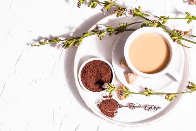 Chicorée-kaffee mit frischen blumen und pulver. natürliches koffeinfreies getränk in einer weißen tasse. alternativer ersatz für kaffee, koffein. weißer putzhintergrund, draufsicht