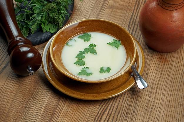 Chikhirtma ist eine traditionelle georgische suppe aus hühnerbrühe, die mit geschlagenen eiern (oder nur eigelb) und zitronenquark eingedickt ist. weiße suppe in keramikschale
