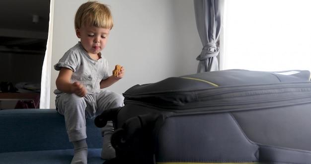 Childe sitzt und isst kekse neben einem koffer