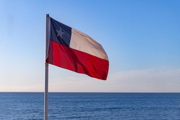 Chilenische flagge mit pazifischem ozean hinten