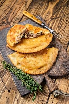 Chilenische gebratene empanadas gefüllt mit rinderhackfleisch, serviert auf einem hölzernen schneidebrett