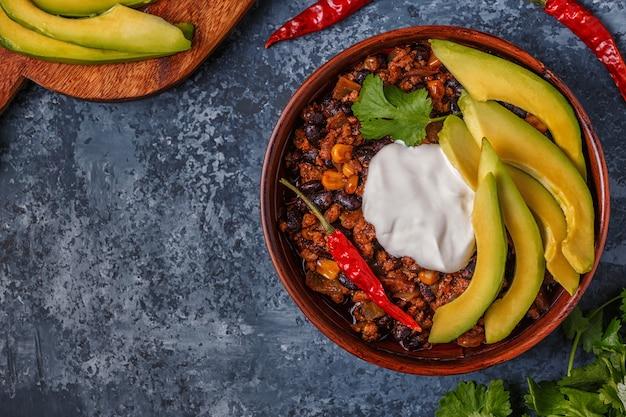 Chili con carne in einer schüssel mit avocado und sauerrahm