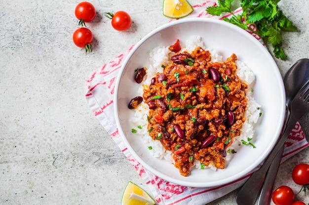 Chili con carne mit reis in der weißen schüssel, draufsicht. rindfleischeintopf mit bohnen in tomatensauce und reis. traditionelles mexikanisches lebensmittelkonzept. Premium Fotos