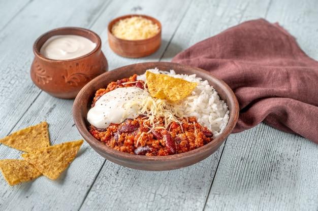 Chili con carne serviert mit reis, geriebenem käse und tortillachips