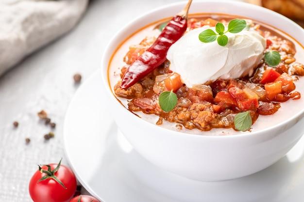 Chili con carne. traditionelles rezept. große portion eintopf mit bohnen, peperoni, gewürzen und frischen kräutern. eine große portion wird in einer schüssel mit frischer sauerrahm serviert.
