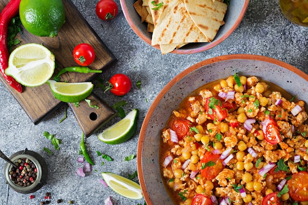 Chili con carne vom truthahn mit kichererbsen serviert mit nachos. chili mit fleisch, nachos, limette, paprika. traditionelles mexikanisches / texanisches essen. ansicht von oben