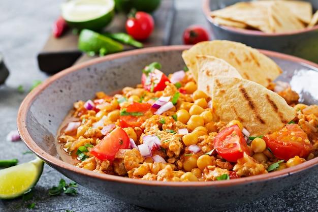 Chili con carne vom truthahn mit kichererbsen serviert mit nachos. chili mit fleisch, nachos, limette, paprika. traditionelles mexikanisches / texanisches essen.