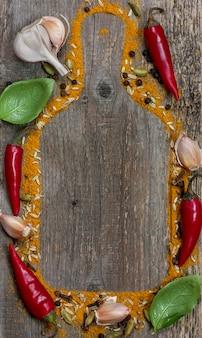 Chili, knoblauch, basilikum, sternanis und gewürze auf altem holzhintergrund