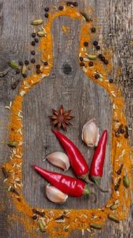Chili, knoblauch, sternanis und gewürze auf altem hölzernen hintergrund