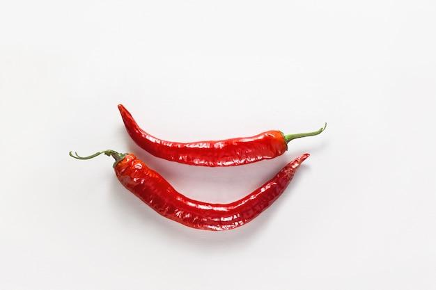 Chili pfeffer lächeln. zwei ganze rote chilischoten. flache lage, draufsicht