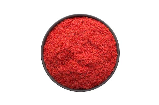 Chili-pfeffer-pulver in tonschale lokalisiert auf weiß