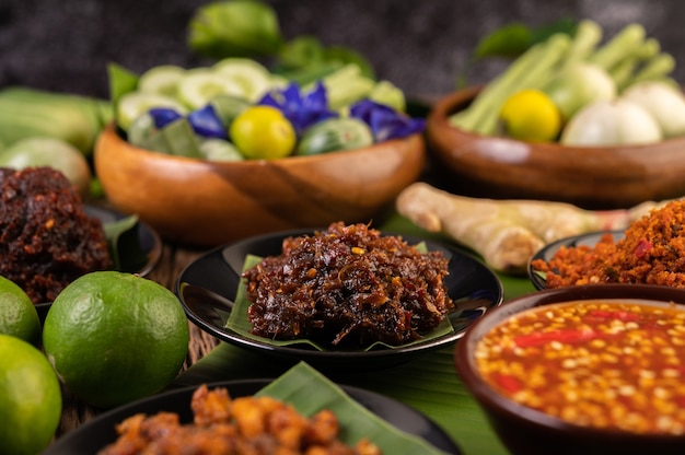 Chilipaste wird auf bananenblättern auf einem teller mit langen bohnen, limette, chili und auberginen serviert.