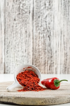 Chilipulver mit rotem pfeffer und holzstück in einer weißen schaufel auf weißer und hölzerner schmutzwand, seitenansicht.