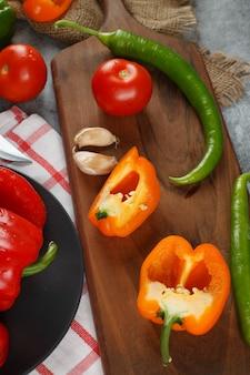 Chilis, gelbe paprika, tomaten und knoblauch auf einem holzbrett. draufsicht.