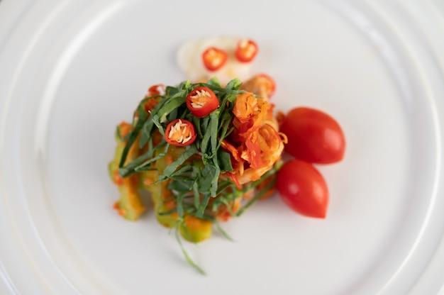 Chilis, kaffirlimettenblätter, bitterer kürbis und tomaten auf einem weißen teller gestapelt.