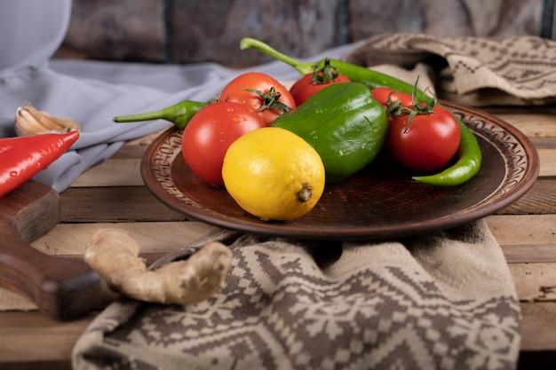 Chilis, tomaten und zitrone auf einer braunen platte
