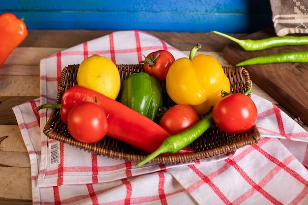 Chilis und tomaten in einer platte auf dem karierten handtuch