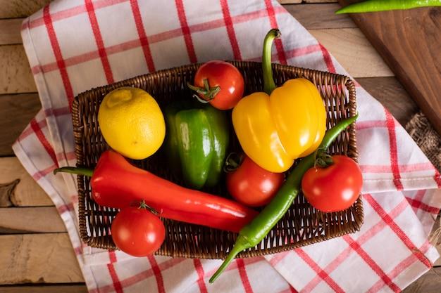 Chilis und tomaten in einer rustikalen platte. draufsicht