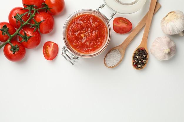 Chilisauce im glas und zutaten auf weißem hintergrund, platz für text. draufsicht