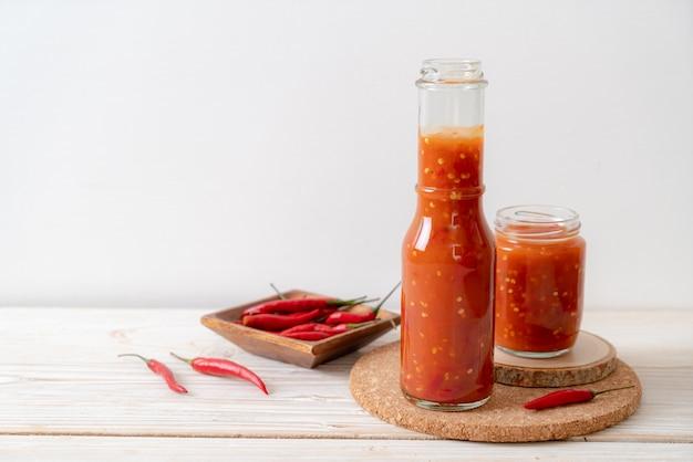 Chilisauce in einem glas und einer flasche isoliert